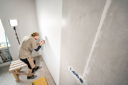 Young repairman aligns with plastic spatula. Worker glueing wallpapers on concrete wall. Repair the apartment. Home renovation concept. White Wallpaper for paint Foto de archivo - 124513222
