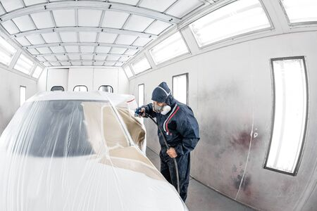 Car service station. Worker painting a white car in special garage, wearing costume and protective gear Фото со стока