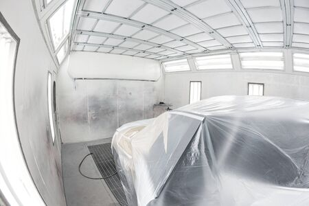 Garage painting car service. Vehicle is covered with protective paper. Repairing car body work after the accident by working sanding primer before painting. Фото со стока