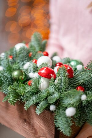 Beautiful festive arrangement of fresh spruce with ball toys in a rustic wooden box. Christmas mood. Bokeh of Garland lights on background.
