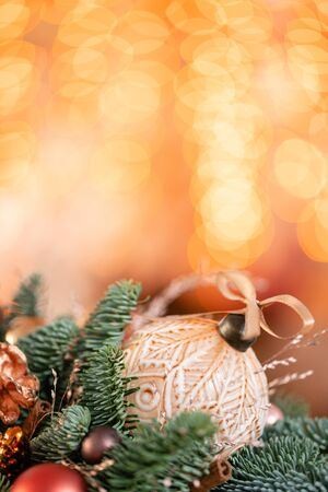 Beautiful festive arrangement of fresh spruce with ball toys in a rustic wooden box. Christmas mood. Bokeh of Garland lights on background