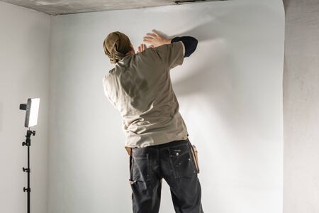 Worker applies a sheet of Wallpaper. Man glueing wallpapers on concrete wall. Repair the apartment. Home renovation concept. White Wallpaper for paint. step by step Foto de archivo - 124513713