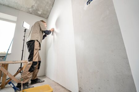 Young man, worker glueing wallpapers on concrete wall. Repair the apartment. Home renovation concept Foto de archivo - 124513776