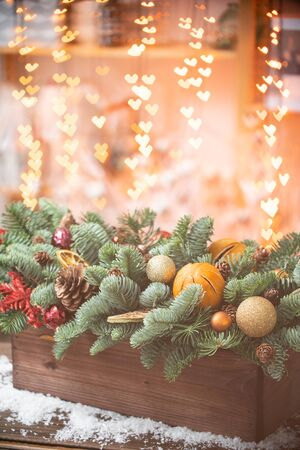 Christmas mood. Beautiful festive arrangement of fresh spruce in a rustic wooden box. Bokeh hearts of Garland lights on background. Decorated with slices orange, gold balls , cones Stock Photo