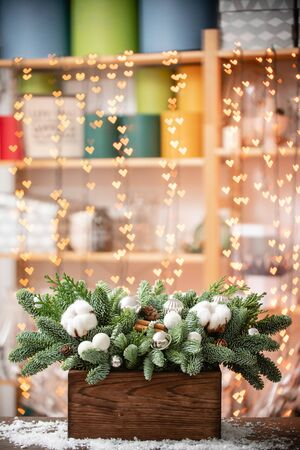 Christmas mood. Beautiful festive arrangement of fresh spruce in a rustic wooden box. Bokeh hearts of Garland lights on background. Decorated with Bells, balls silver, white cotton and cinnamon Stock Photo