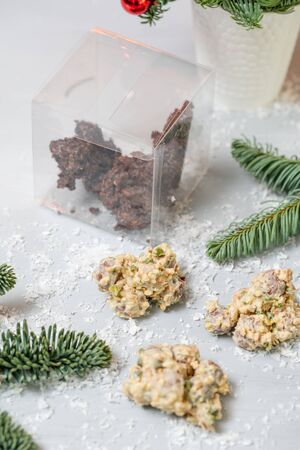 Rocks with chocolate and nuts. Christmas theme. Healthy sweet dessert snack. Granola bar with nuts, fruit, chocolate and berries. Garland lamps bokeh on background. Copy space Imagens