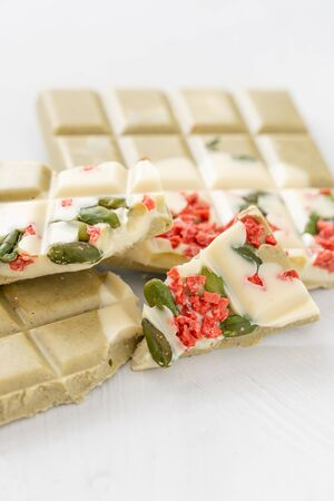 Handmade chocolates bar. White chocolate bar with pistachio nuts and dried fruit cherries. Copy space. Light key on white Desk Stock Photo