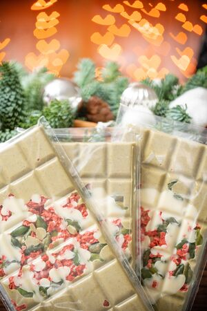 Handmade chocolates bar. Christmas theme. White chocolate bar with pistachio nuts and dried fruit cherries. Garland lamps bokeh on background. Copy space