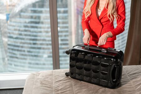 Close-up unpacks suitcase Young blond businesswoman arrives in a hotel room with black suitcase. Woman in red coral business suit. Stock Photo