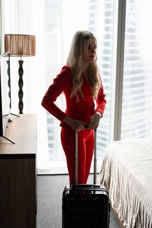 Young blond businesswoman arrives in a hotel room with black suitcase. Woman in red coral business suit. Young girl packs suitcase.
