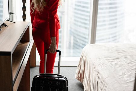 Close-up the hand holding the handle suitcase. Businesswoman arrives in a hotel room with black suitcase. Woman in red coral business suit. Stock Photo