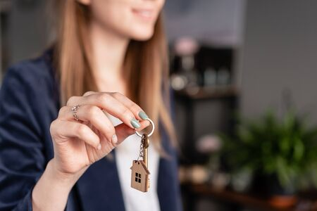 House key rotates on the finger in womans hands. Young pretty woman smiles. Modern light lobby interior. Real estate, hypothec, moving home or renting property