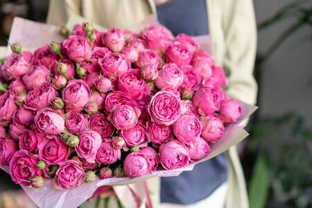 Small Beautiful bouquet of mixed flowers in woman hand. Floral shop concept . Beautiful fresh cut bouquet. Flowers delivery.