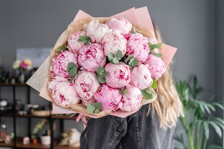 Pink peonies in womans hands. Beautiful peony flower for catalog or online store. Floral shop concept . Beautiful fresh cut bouquet. Flowers delivery.