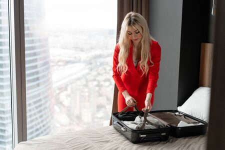 Stewardess in red uniform arrives in a hotel room with black suitcase. Rest in the transit city before the return flight. Young blond Woman in red coral suit unpacks suitcase Reklamní fotografie