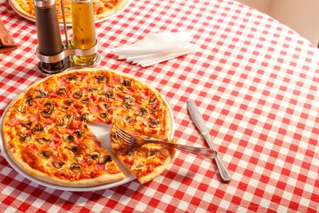 Pizza with ham and mushrooms. Delicious hot food sliced and served on white platter. Menu photo, Italian fast food. 스톡 콘텐츠