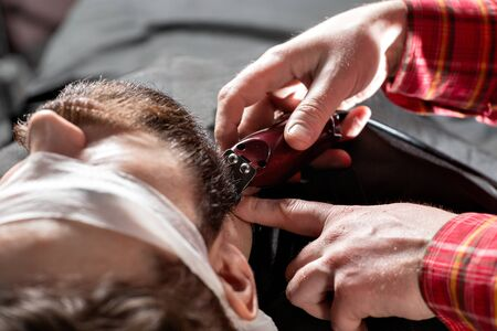 Beard cutting, face care. Barber work with clipper machine in barbershop. Professional trimmer tool cuts beard and hair of young guy in barber shop salon.