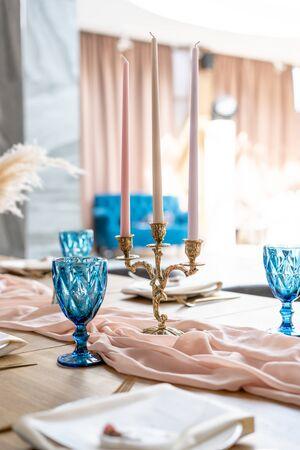 Luxus Abendessen Bankett im Restaurant. Schöne und exquisite Dekoration der Hochzeitsfeier. Bankett serviert Tisch mit einer beige rosa Tischdecke, Teller und Kerzenhalter mit Kerzen.