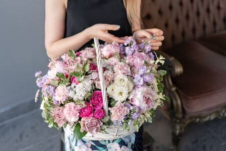 Flower arrangement in Wicker basket. Beautiful bouquet of mixed flowers in woman hand. Floral shop concept . Handsome fresh bouquet. Flowers delivery