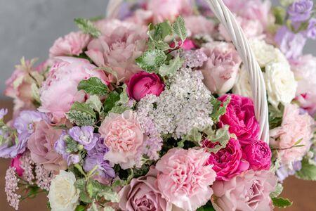 Arreglo floral en canasta de mimbre. Hermoso ramo de flores mixtas en mano de mujer. Concepto de tienda floral. Hermoso ramo fresco. Entrega de flores