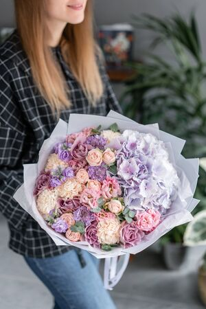 Beautiful bouquet of mixed flowers in woman hand. Floral shop concept . Handsome fresh bouquet. Flowers delivery. Red and pink color.