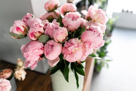 The counter of the flower shop. Pink peonies in a metal vase. Beautiful peony flower for catalog or online store. Floral shop concept . Beautiful fresh cut bouquet. Flowers delivery