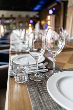 Wine glasses in the foreground. Wedding Banquet or gala dinner. The chairs and table for guests, served with cutlery and crockery. Reklamní fotografie