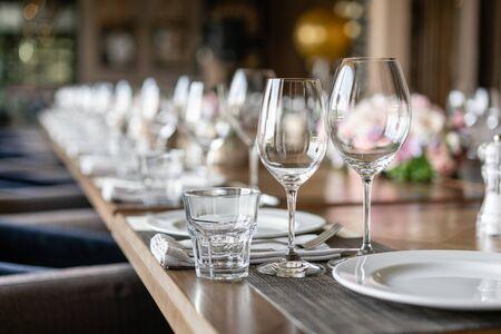 Kieliszki do wina na pierwszym planie. Bankiet weselny lub uroczysta kolacja. Krzesła i stół dla gości, serwowane wraz ze sztućcami i naczyniami.