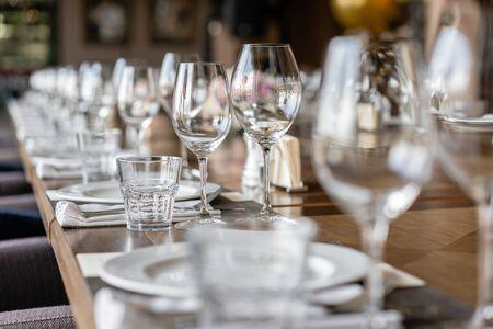 Kieliszki do wina na pierwszym planie. Bankiet weselny lub uroczysta kolacja. Krzesła i stół dla gości, serwowane wraz ze sztućcami i naczyniami. Zdjęcie Seryjne