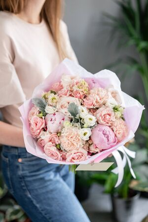 Pink peonies. Beautiful bouquet of mixed flowers in woman hand. Floral shop concept . Handsome fresh bouquet. Flowers delivery. Red and pink color.