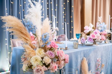 Blue tablecloth, plates and candlesticks with candles. Luxury dinner Banquet in the restaurant. Beautiful and exquisite decoration of the wedding celebration.