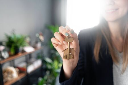 House key rotates on the finger in womans hands. Young pretty woman smiles. Modern light lobby interior. Real estate, hypothec, moving home or renting property.