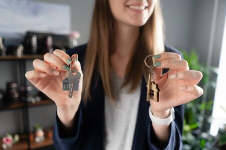 two house keys in womans hands. Young pretty woman smiles. Modern light lobby interior. Real estate, hypothec, moving home or renting property.