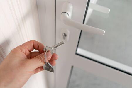 Modernes helles Lobby-Interieur. Männer übergeben Schlüssel mit Hausschlüsselbund. Immobilien, Umzug oder Miete. Hypothekenkonzept.
