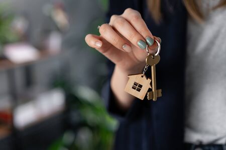 Concept of renting an apartment. House key in womans hands. Young woman. Modern light lobby interior. Real estate, hypothec, moving home or renting property.