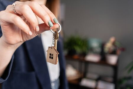 In the foreground house key in womans hands. Young pretty woman. Modern light lobby interior. Real estate, hypothec, moving home or renting property.