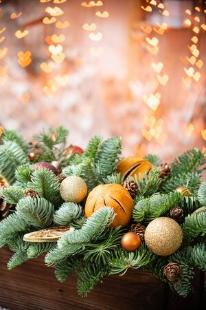 Christmas mood. Beautiful festive arrangement of fresh spruce in a rustic wooden box. Bokeh hearts of Garland lights on background. Decorated with slices orange, gold balls , cones Reklamní fotografie