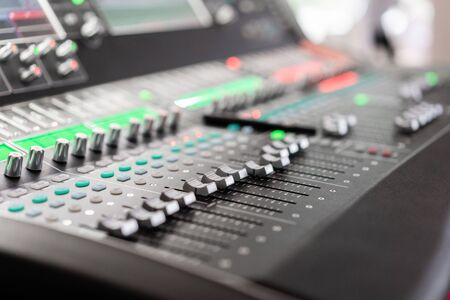 Sound mixer. Professional audio mixing console with lights, buttons, faders and sliders. Stock Photo - 128831388