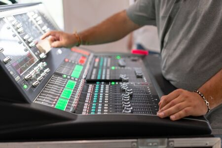 Male hand on control Fader on console. Sound recording studio mixing desk with engineer or music producer