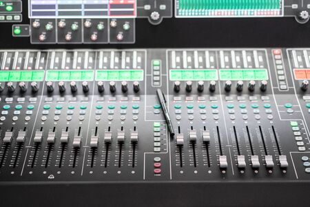 Sound mixer. Professional audio mixing console with lights, buttons, faders and sliders. Stock Photo - 128831430