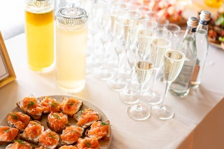 the buffet at the reception. Glasses of wine and champagne. Assortment of canapes on wooden board. Banquet service. catering food, snacks with cheese, jamon, prosciutto and fruit