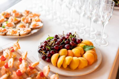 Fresh Fruit platter buffet at business or wedding event venue. Self service or all you can eat - cherries, nectarine, grapes and pineapple. Table with cold drink and snacks and tableware