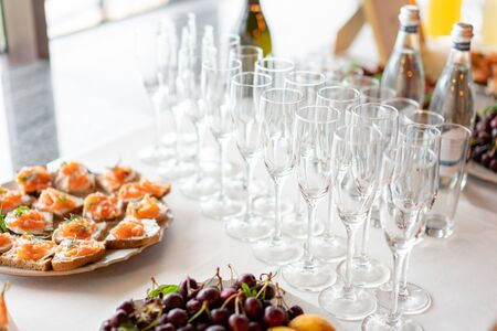 reception. Table top full of glasses of sparkling white wine with canapes and antipasti in the background. champagne bubbles