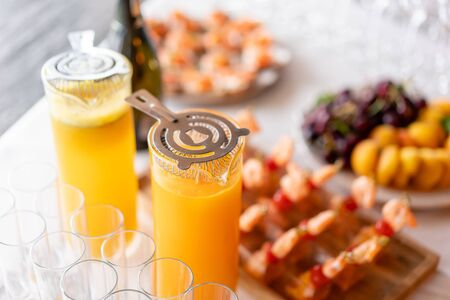 Glass bank of lemonade with sliced citrus fruits on a buffet table. Summer party outdoor. Detox. Imagens - 128831439