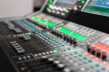 od adjusters and red buttons of a mixing console. It is used for audio signals modifications to achieve the desired output. Applied in recording studios, broadcasting, television. Stock Photo - 128831483