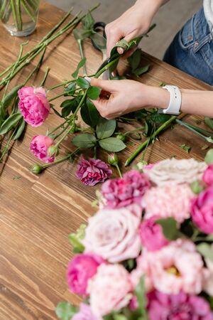 Floristería mujer crea arreglo floral en una cesta de mimbre. Hermoso ramo de flores mixtas. Concepto de tienda floral. Hermoso ramo fresco. Entrega de flores Foto de archivo