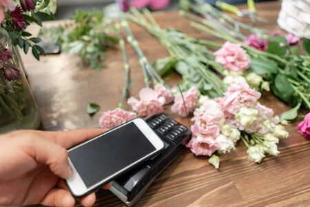 Concept contactless payment. Making payment with smartphone and pos terminal, printed check. Floral shop concept . Flowers delivery Stock fotó