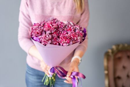 Pink and purple carnation flowers . Beautiful bouquet of mixed flowers in woman hand. Floral shop concept . Handsome fresh bouquet. Flowers delivery.