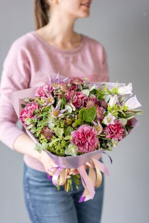 Beautiful bouquet of mixed flowers in woman hand. Floral shop concept . Handsome fresh bouquet. Flowers delivery. green and pink color.