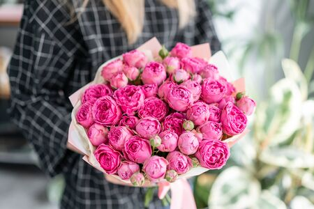 Pink and purple roses . Beautiful bouquet of mixed flowers in woman hand. Floral shop concept . Handsome fresh bouquet. Flowers delivery.